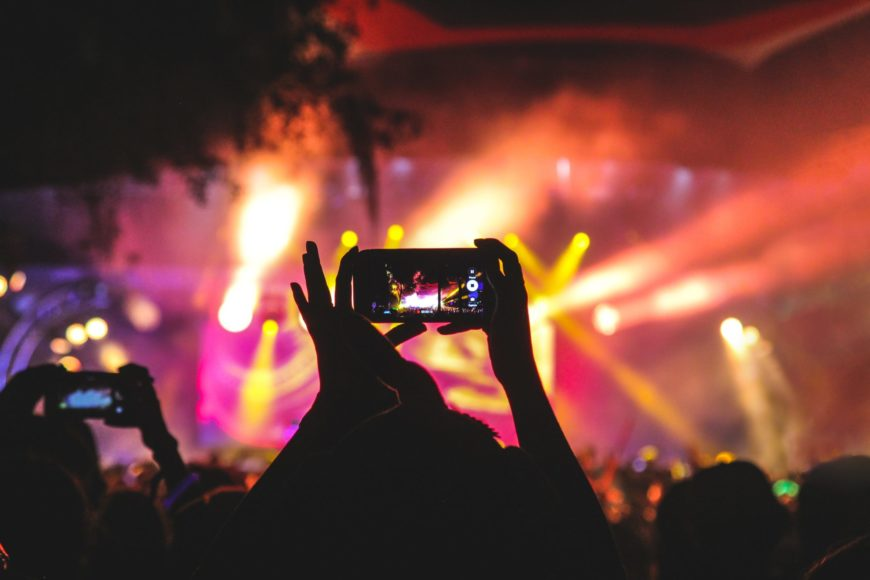 Crowd watches a concert through their phone and is live-streaming it to even greater audiences