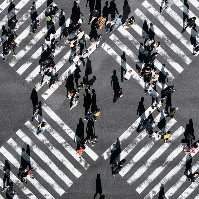 Influencers drawing people across a busy city street different directions