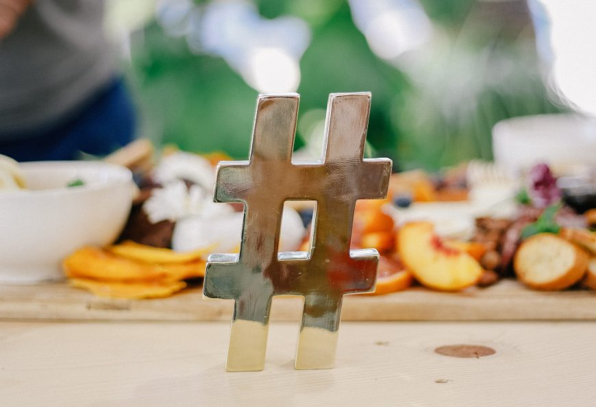 A metallic hashtag with a plate of fruit in the background.
