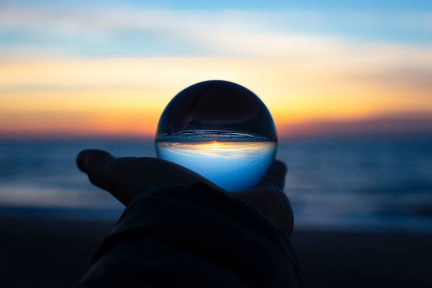 A crystal ball being held up to a horizon